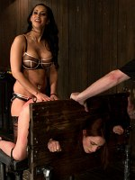 Amber Rayne bound in wooden stocks